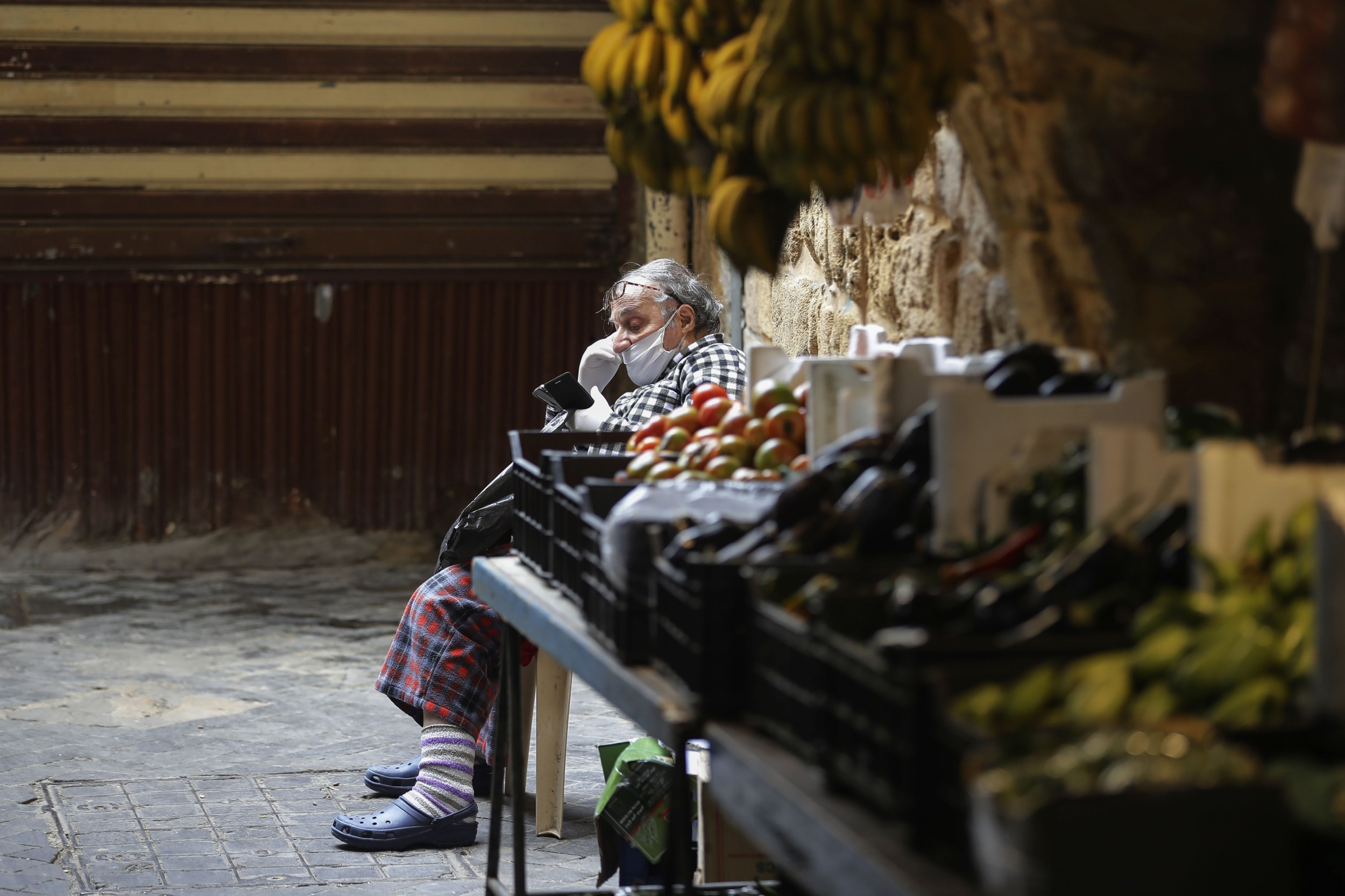 A Lebanese man sits by a fresh produce stall in the market of the historic part of the southern coastal city of Saida on 6 April 2020 (AFP)