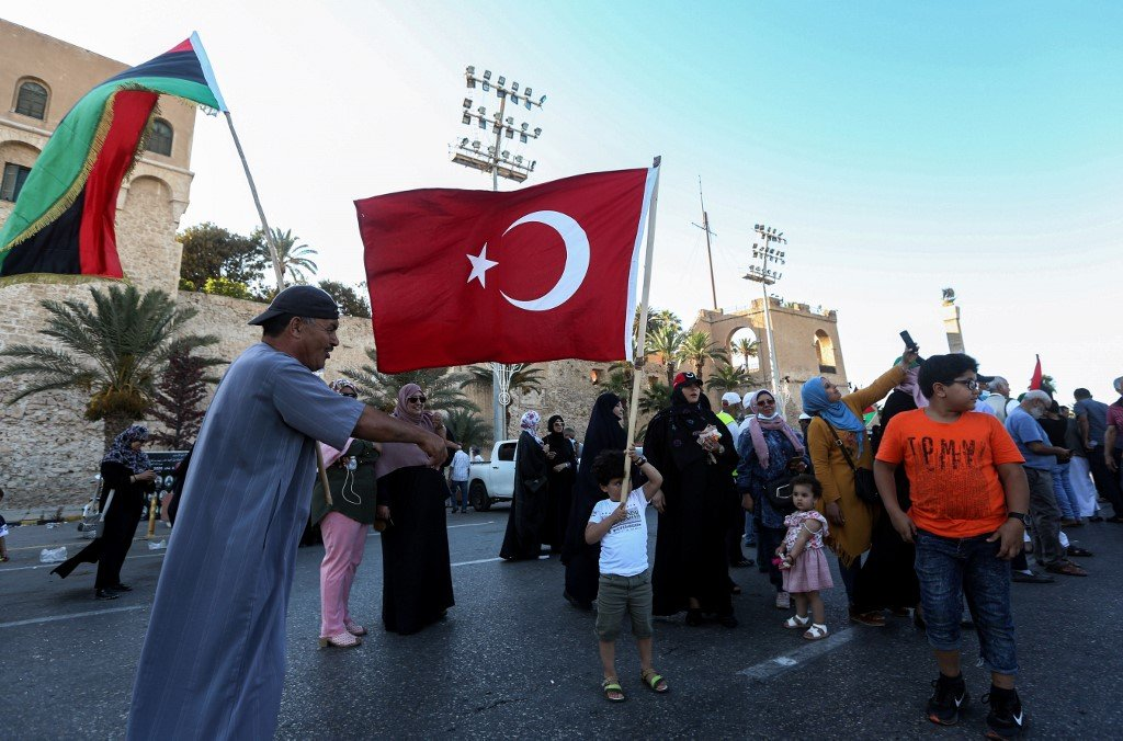 People wave Libyan and Turkish flags during a demonstration in Tripoli on 21 June (AFP)