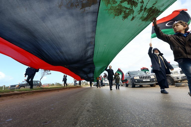 In February 2019, Libyans carry a giant national flag in the capital Tripoli to mark the the upcoming eighth anniversary of the Libyan revolution (AFP)