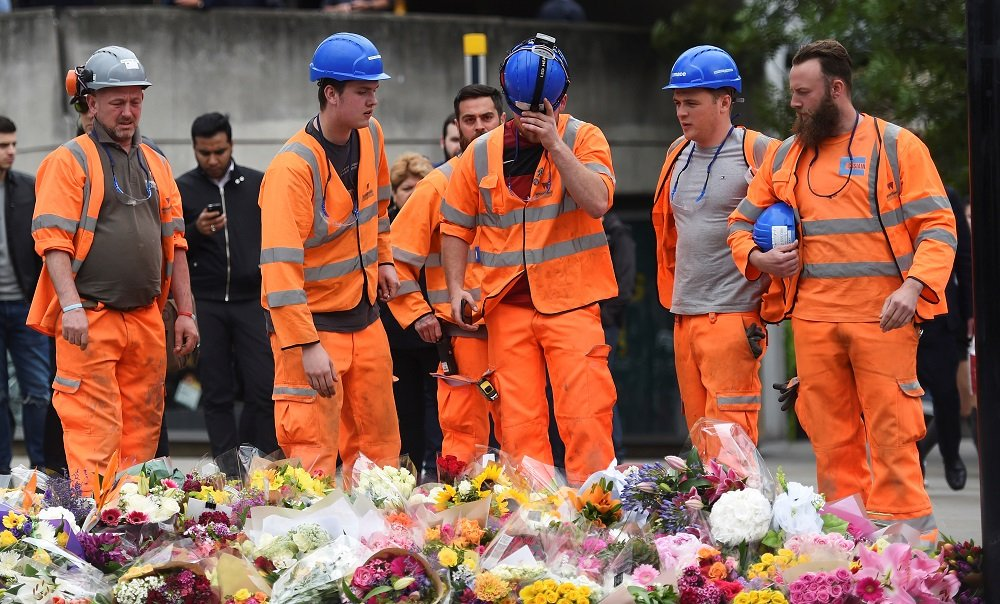 Construction workers lay flowers near the scene of the London Bridge attack in June 2017 (Reuters)
