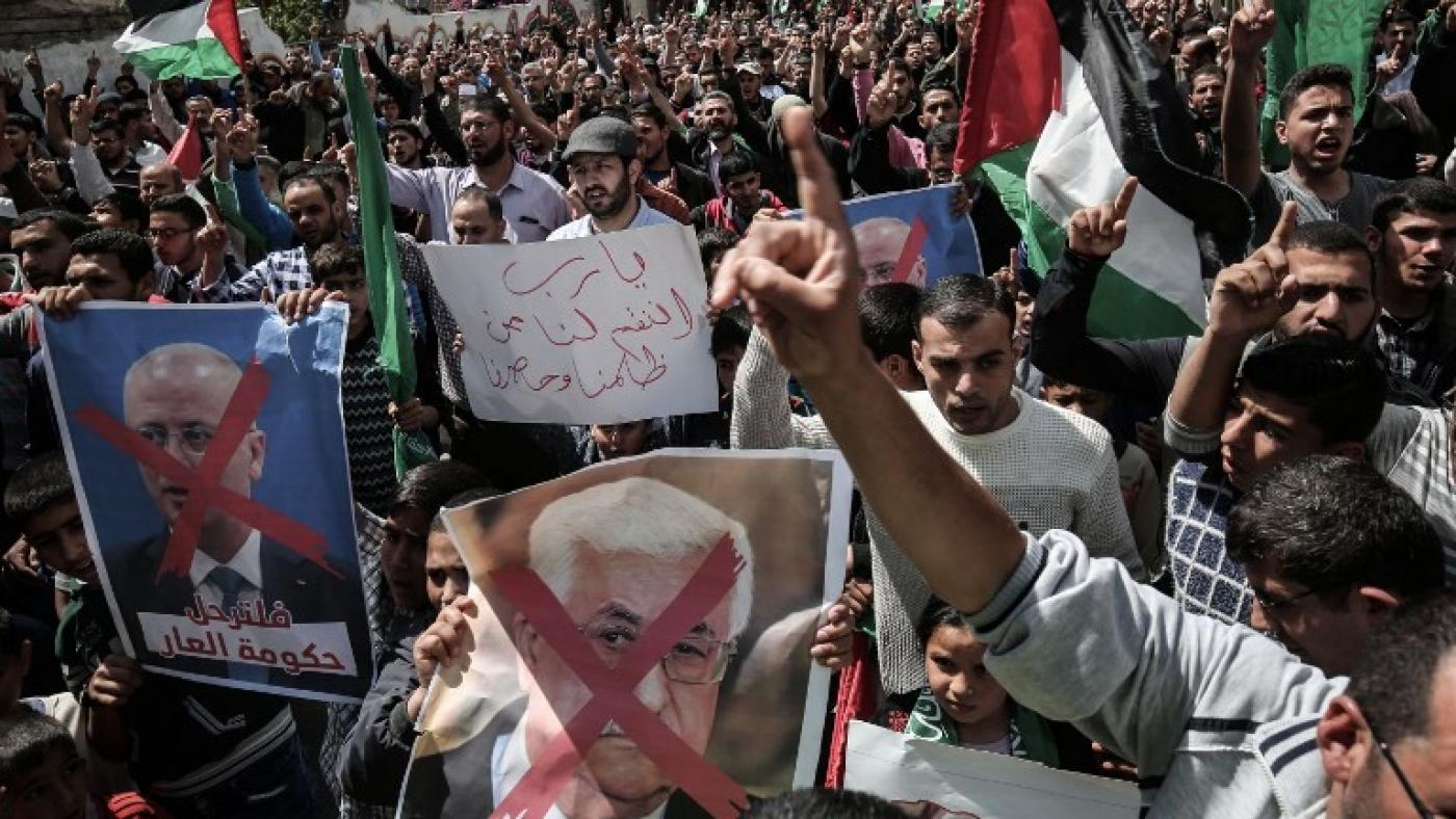 Demonstrators in Gaza hold up portraits of Mahmoud Abbas in protest against the PA president (AFP)
