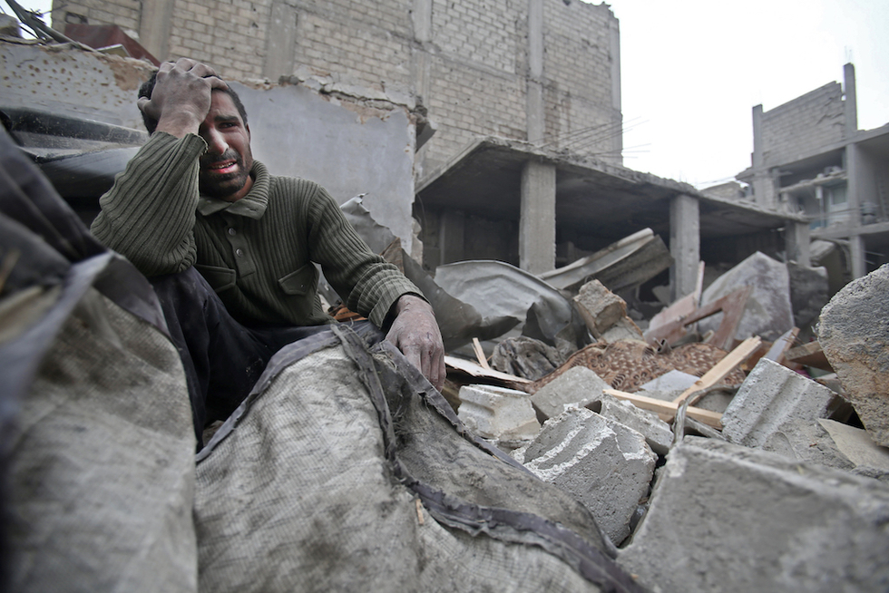 A Syrian man mourns over his destroyed home in the rebel-held besieged town of Arbin, in the Eastern Ghouta region on the outskirts of the capital Damascus (AFP)