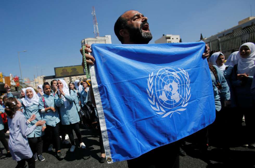Palestinian demonstrator holds UN flag during a rally against a U.S. decision to cut funding to UNRWA