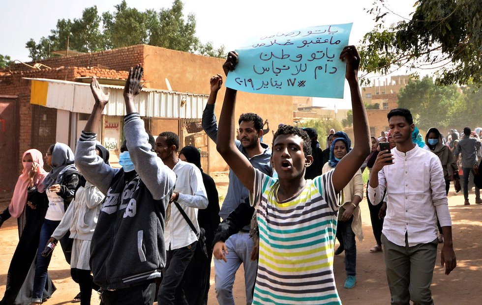 Protesters march towards presidential palace in Khartoum on Thursday (Reuters)