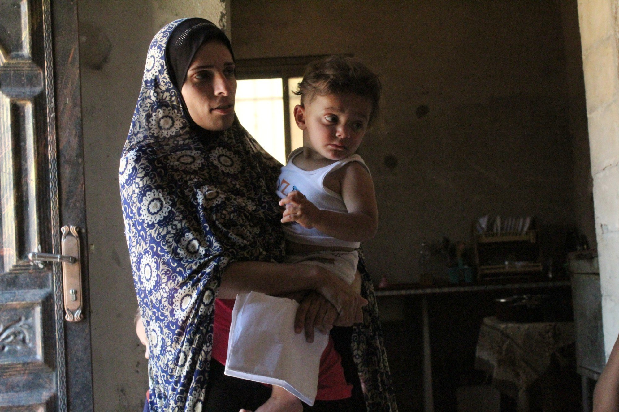 Maye Barakat holds her one-year-old son, who has respiratory problems, and his medical papers (MEE/Megan Giovannetti)