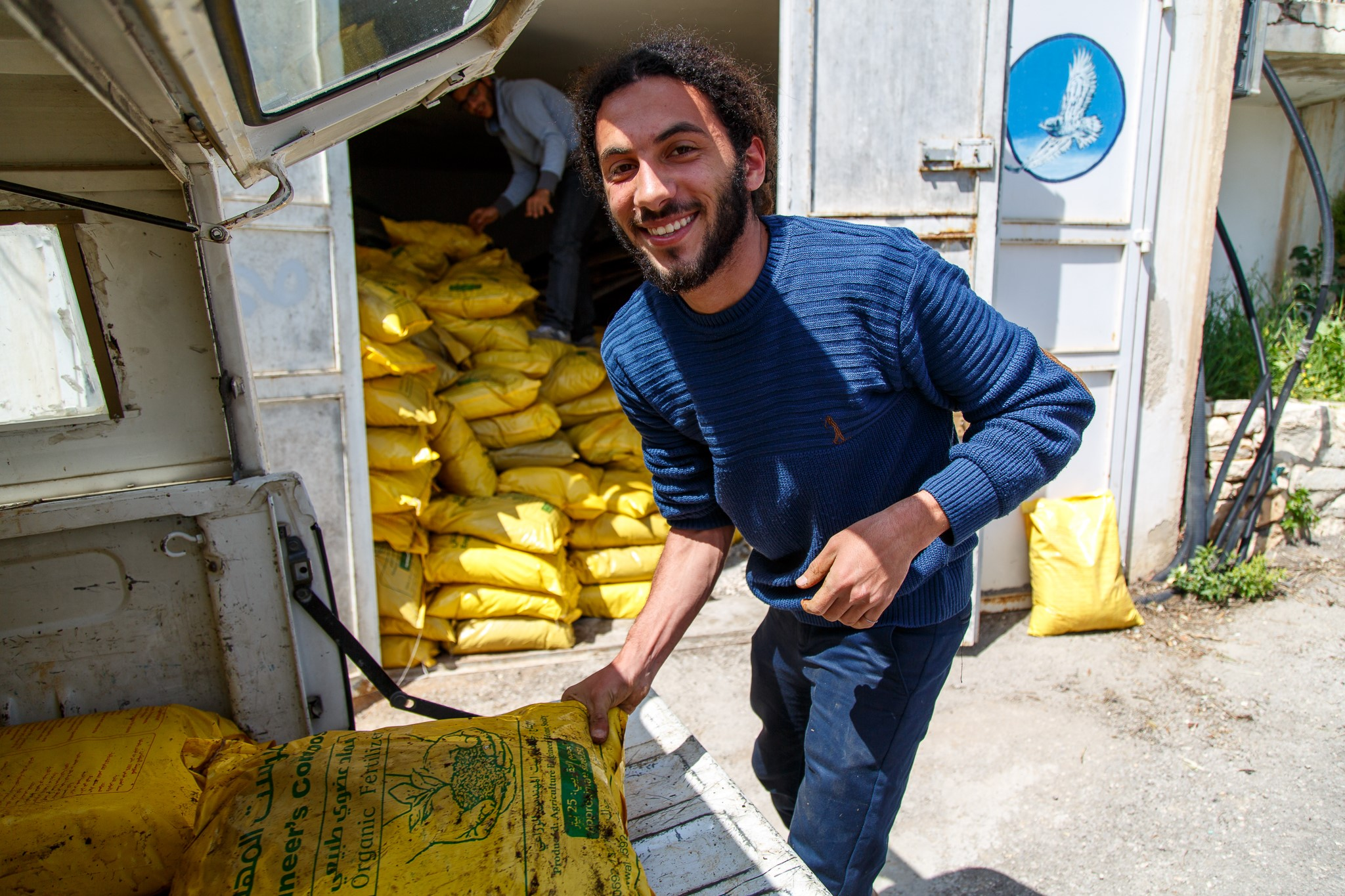 Co-ordinator of the cultural heritage centre at the Museum, Mohammad Najajrah helps to move the compost