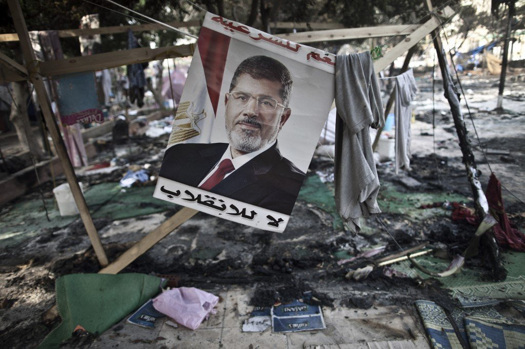 A picture of former Egyptian President Mohamed Morsi hangs in Rabaa Square in 2013 (AFP)