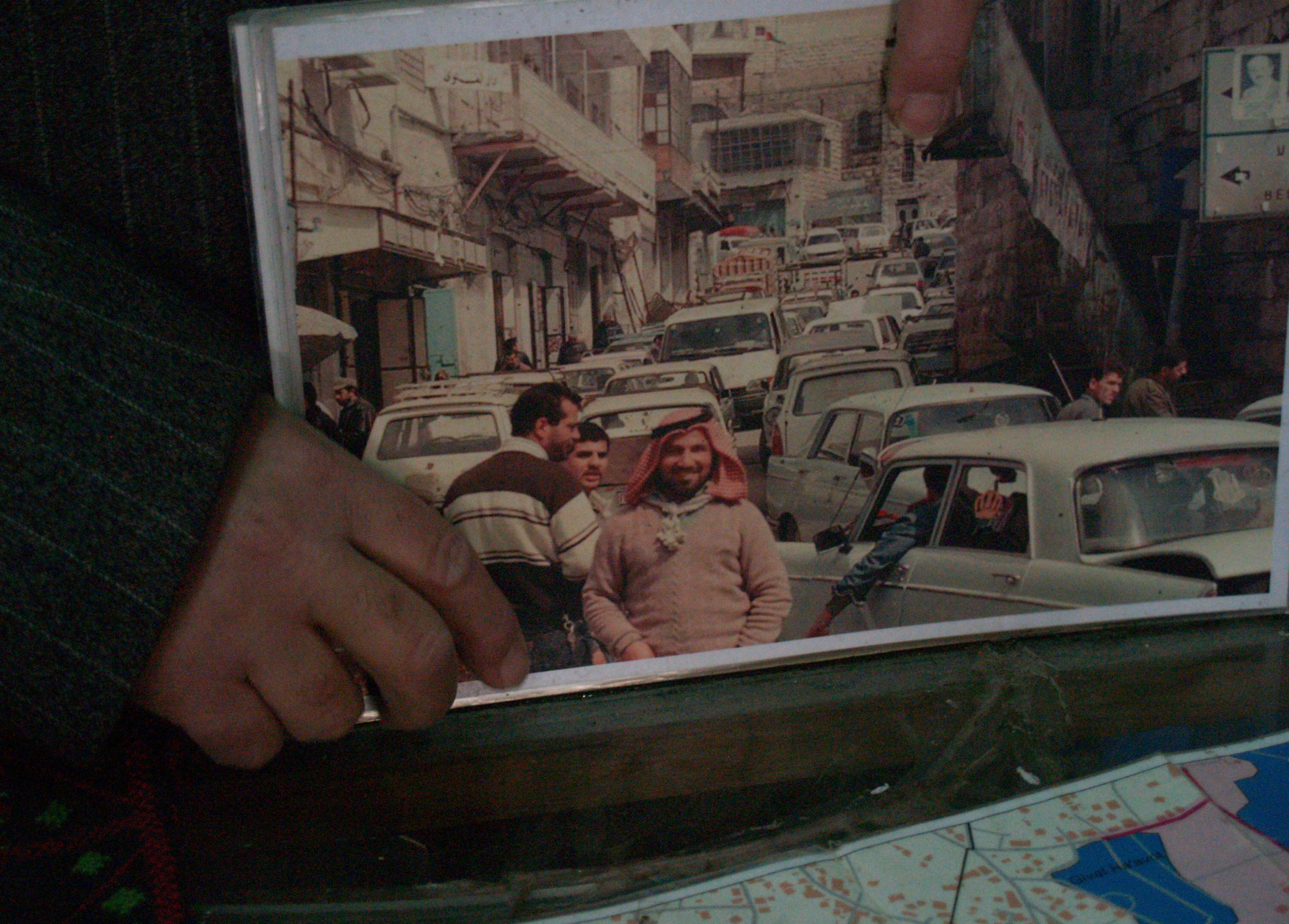 Munir shows a photo of Shuhada Street in the days before the massacre, back when the road was the bustling centre of Hebron (MEE/Megan Giovannetti)