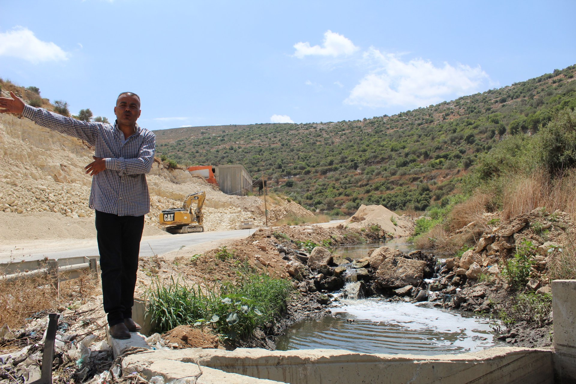 Murad Samara stands near part of the toxic stream of sewage stream right by the beginning of the municipality-constructed pipe (MEE/Megan Giovannetti)
