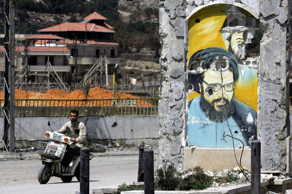 A motorcycle passes a ruined portrait of late Hezbollah leader Abbas Musawi, who was killed in an Israeli operation in 1992, in the southern Lebanese town of Bint Jbeil in 2006 (AFP)
