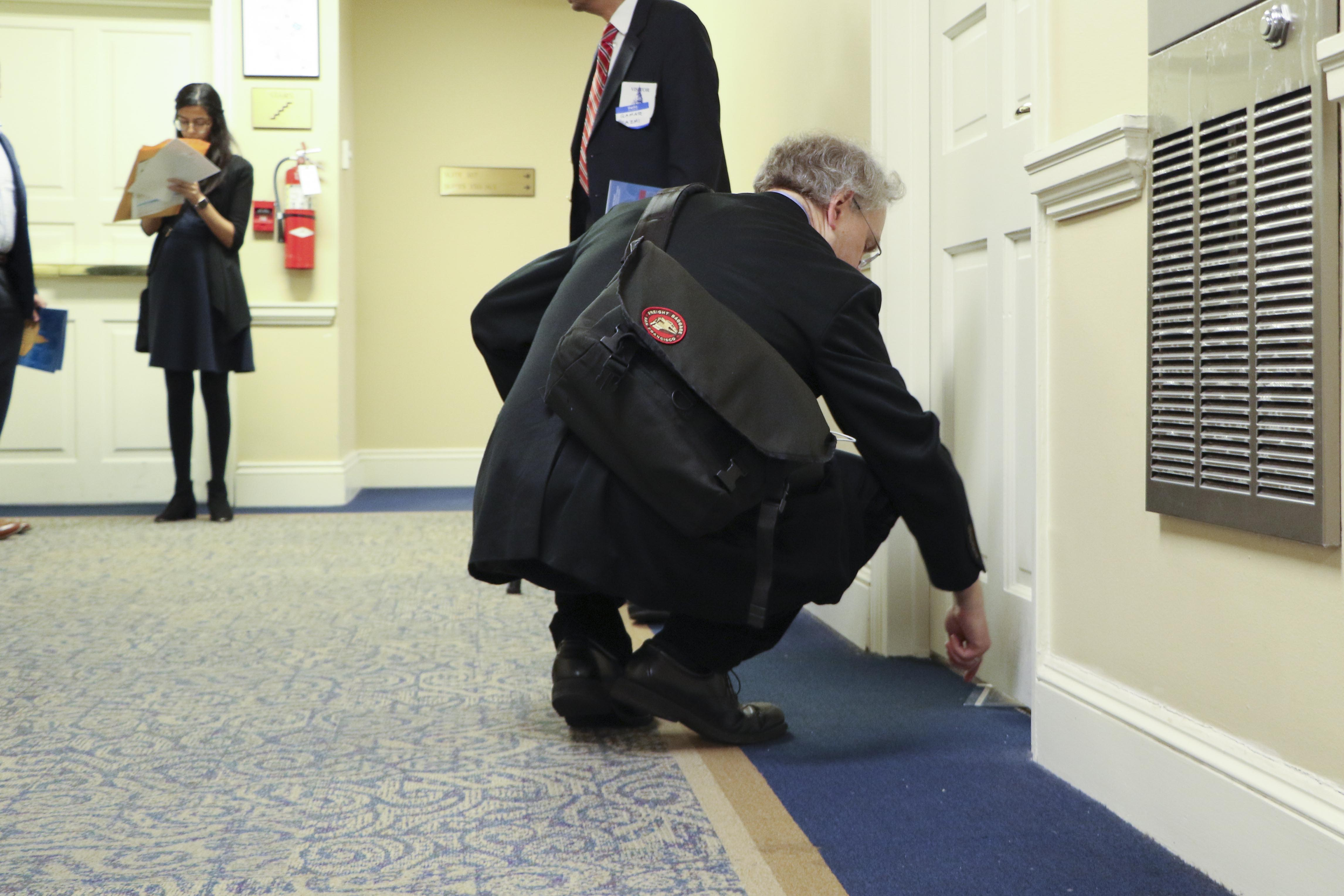 A man slips literature under the door of a delegate who is not in their office.
