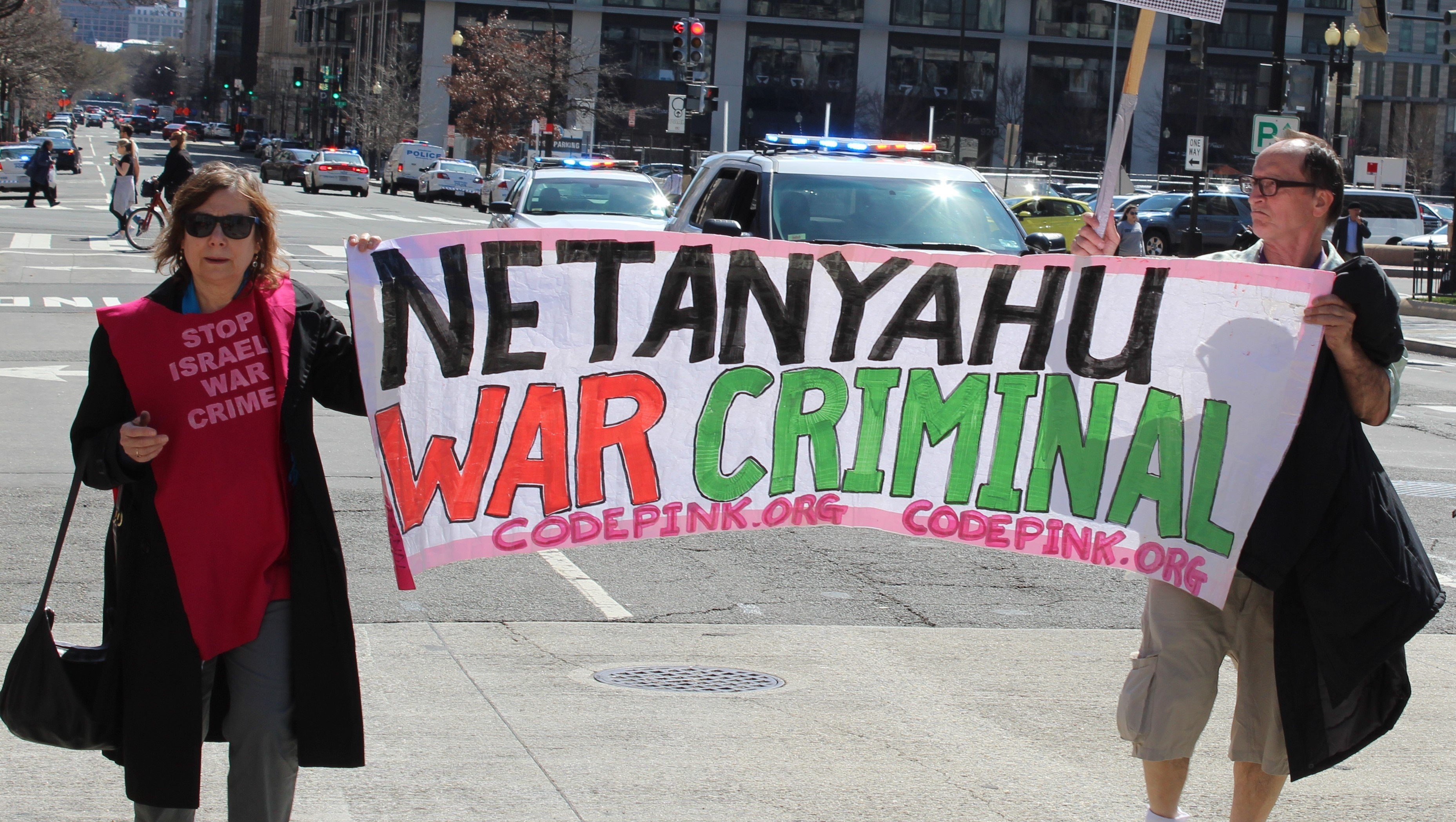 Protesters hold sign outside AIPAC conference (MEE/Ali Harb)