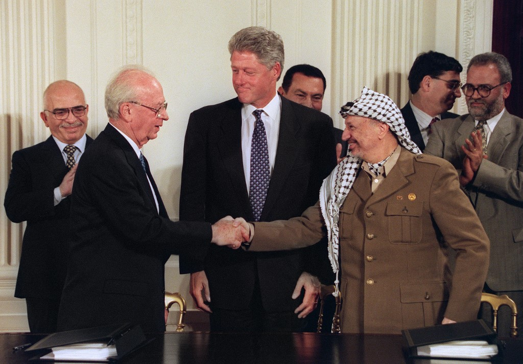 Former US President Bill Clinton observes as former Israeli Prime Minister Yitzhak Rabin and former PLO chairman Yasser Arafat shake hands in Washington in 1995 (AFP)