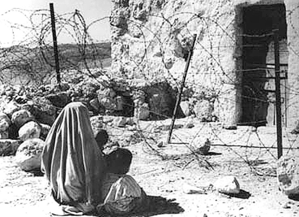 A Palestinian refugee and her child are separated from their home after the 1948 war (AFP)