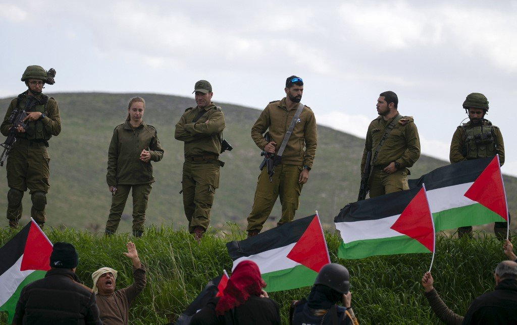 Israeli soldiers stand guard as Palestinians protest against the annexation of the Jordan Valley on 29 February (AFP)