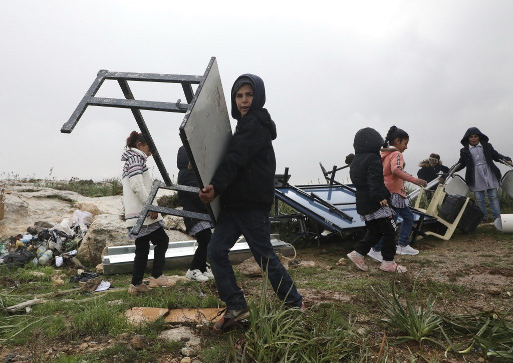 Palestinian children move their classroom furniture after Israeli forces dismantled a school facility on the outskirts of Hebron in the occupied West Bank on 19 February (AFP)