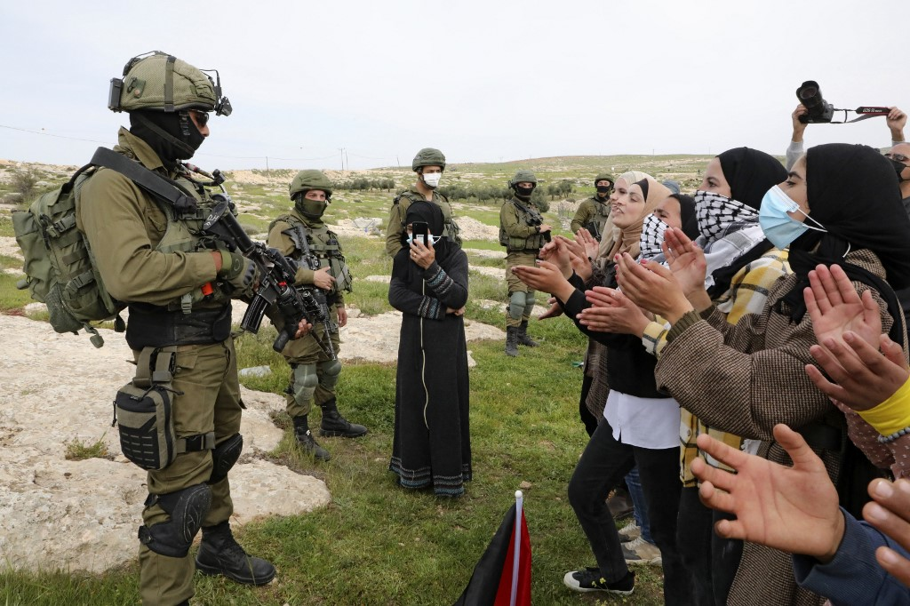 Palestinian women chant slogans as Israeli soldiers stand guard during a protest in the Palestinian village of Susya in the occupied West Bank on 14 March 2021 (AFP)