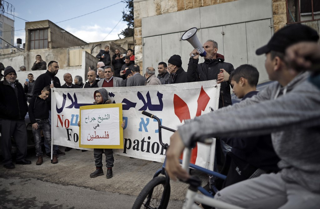 shout slogans during a protest near the house of a Palestinian family, which an Israeli court had ordered to be evicted while declaring Israeli settlers to be the legal owners, in
