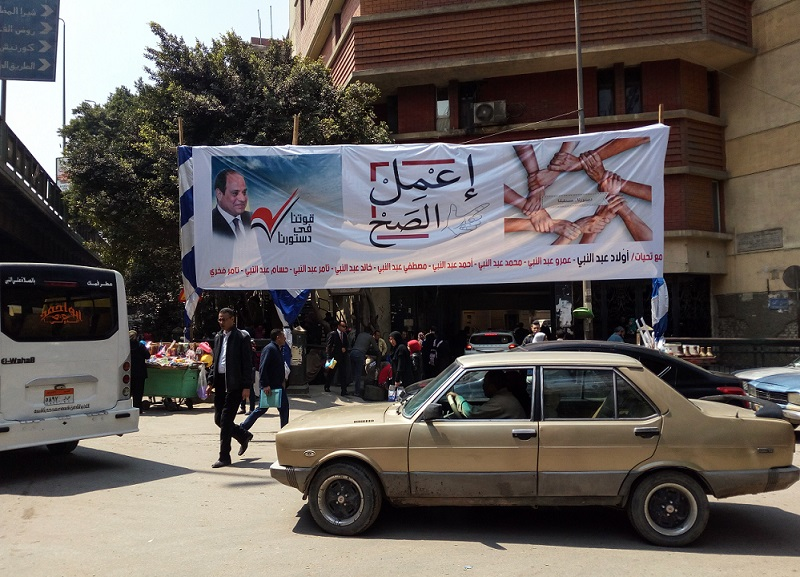 'Tick the box' says the campaign poster in Cairo which lists around 10 names of those who presumably sponsored the banner (MEE)