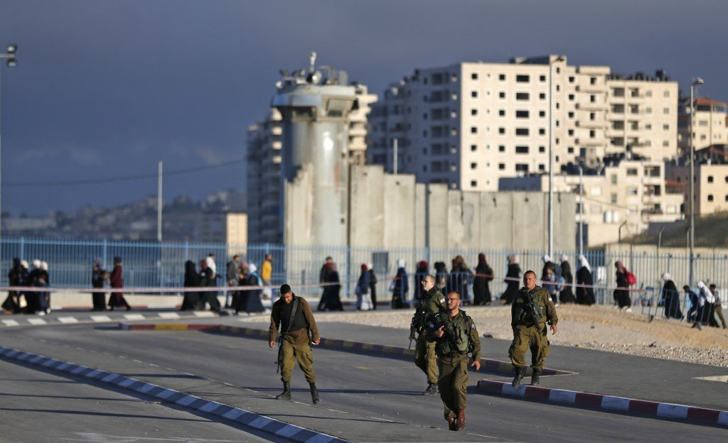 Israeli soldiers walk near Jerusalem's Qalandia checkpoint on 10 May (AFP)