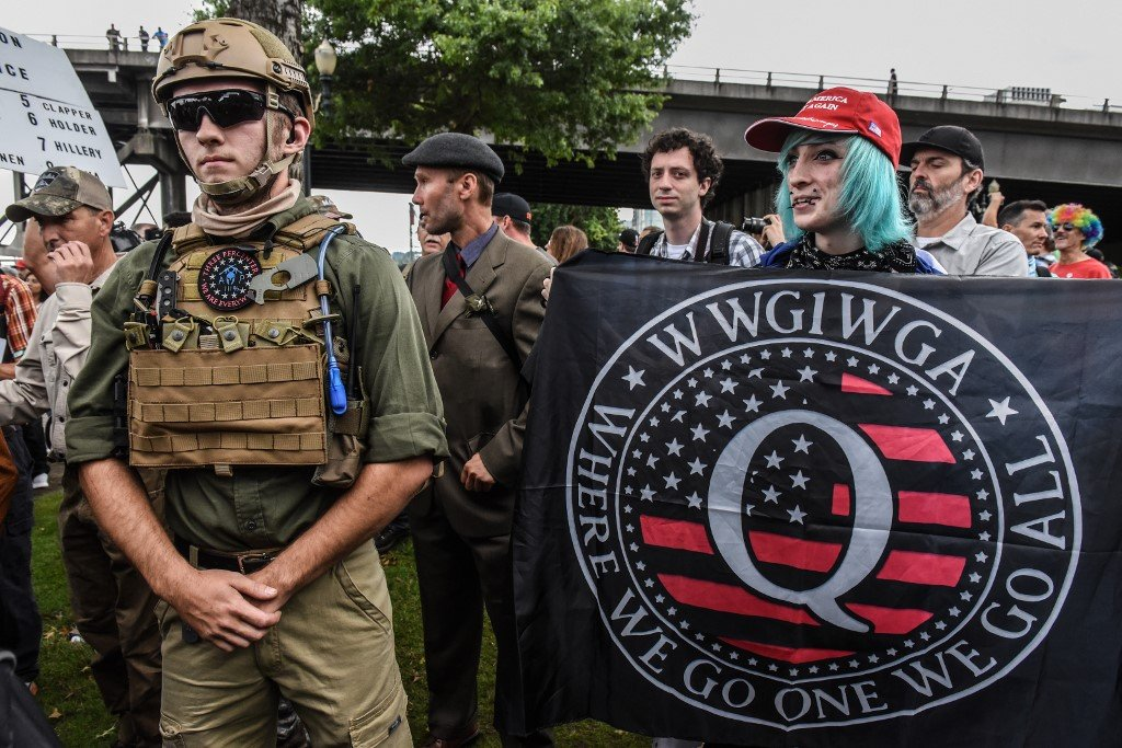 A person holds a banner referencing the QAnon conspiracy theory during an alt-right rally in Portland, Oregon, in August 2019 (AFP)