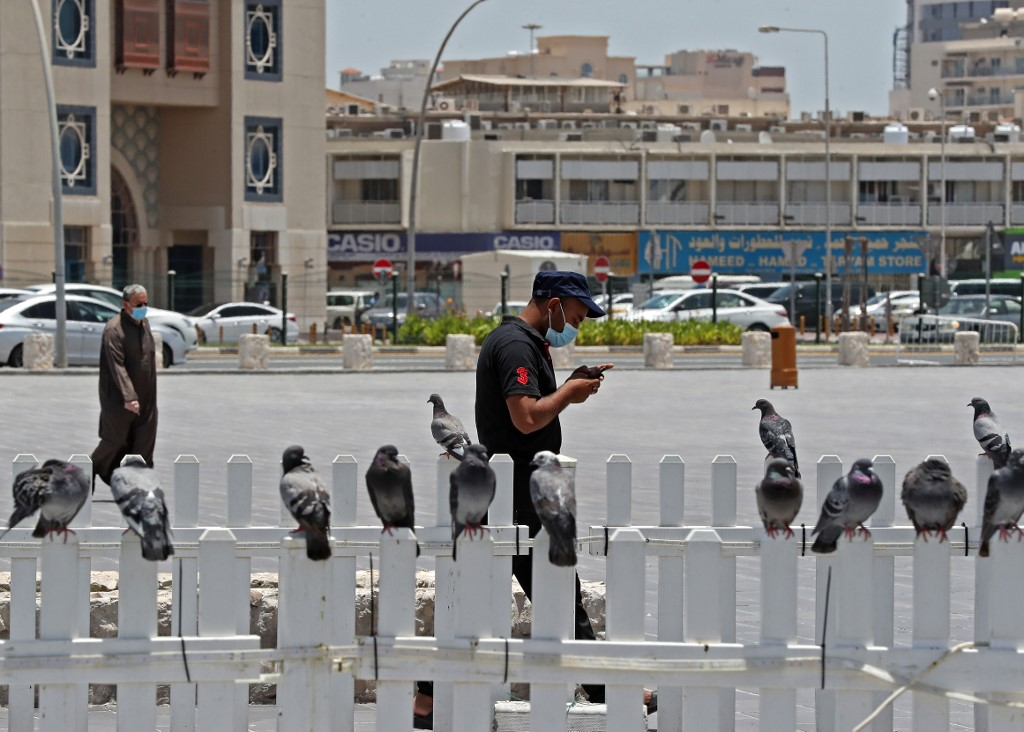 A man wearing a protective mask checks his phone as he walks by at Qatar's touristic Souq Waqif bazar in the capital Doha, on May 17, 2020,