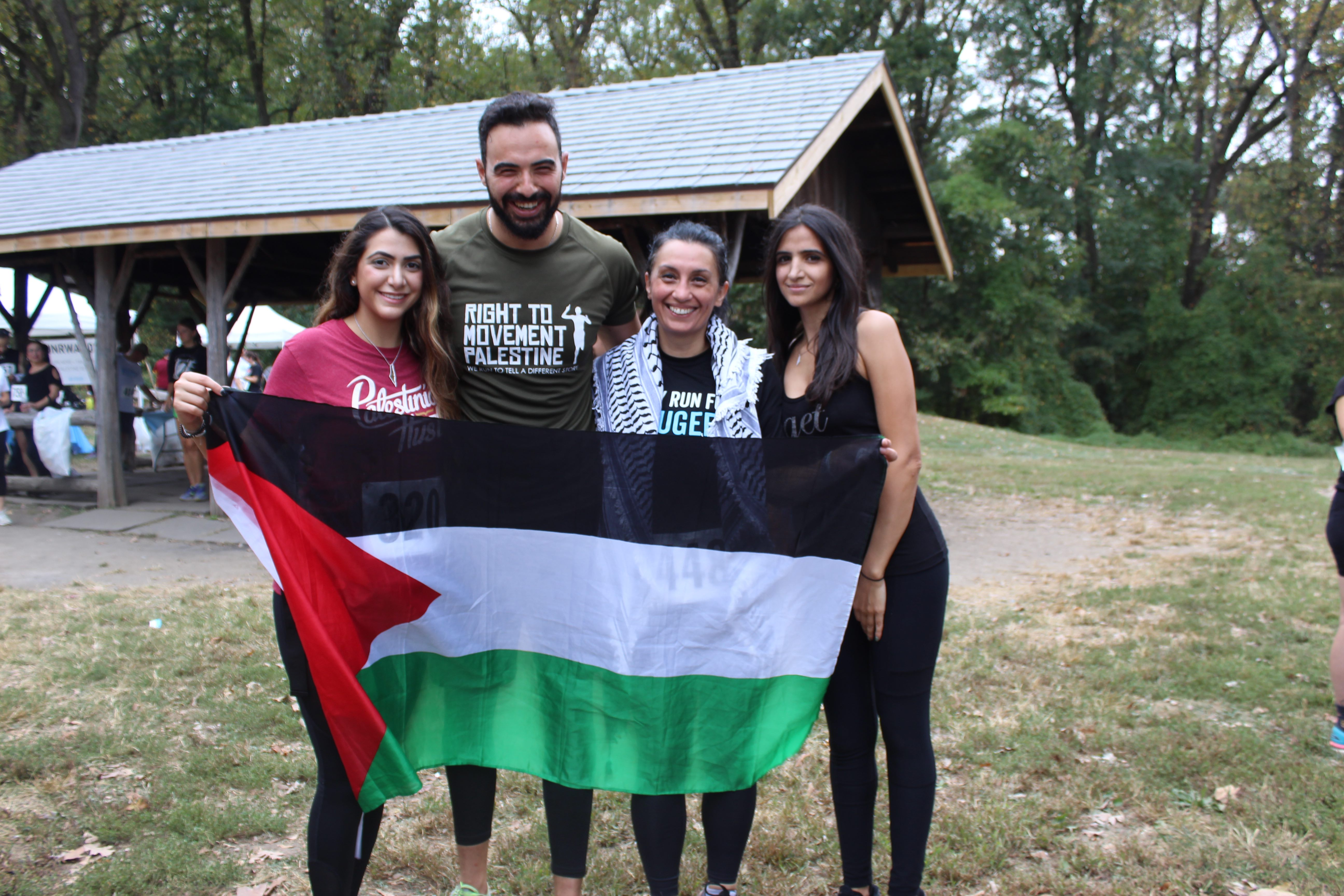 Rania Qawasma, with a kuffiyeh wrapped around her shoulders, holds up a Palestinian flag with three other runners who completed both races (MEE/Sheren Khalel
