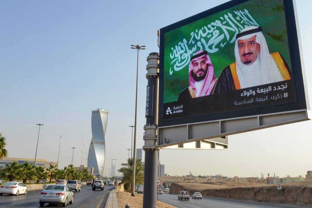 An electronic billboard bears the portraits of Saudi King Salman bin Abdulaziz and his son, the crown prince, in Riyadh on 18 November (AFP)