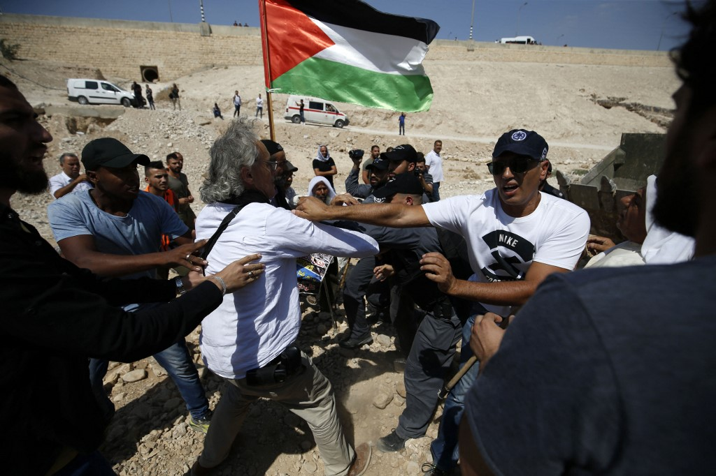 Israeli forces scuffle with American-French law professor Frank Romano (white shirt L) and other Palestinian protestors, with a Palestinian national flag in the background, on September 14, 2018,