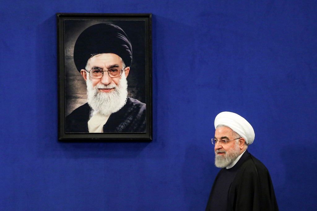 Iranian President Hassan Rouhani walks past a portrait of Supreme Leader Ayatollah Ali Khamenei in Tehran on 16 February (AFP)