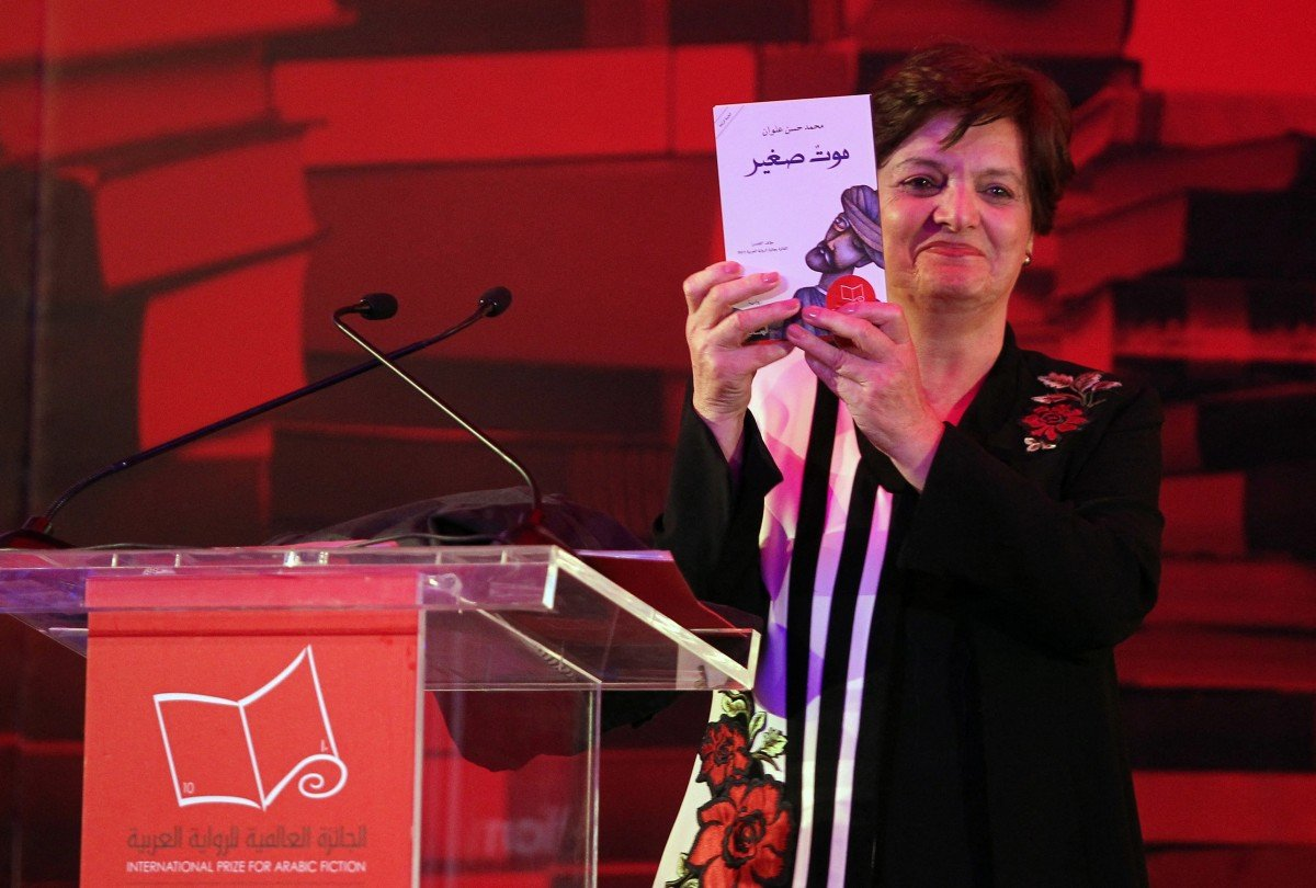 Palestinian novelist and chair of the judging committee Sahar Khalifeh poses for a photo with the winning book of the 2017 International Prize for Arabic Fiction by Saudi Arabian writer Mohammed Hasan Alwan in 2017 (AFP)