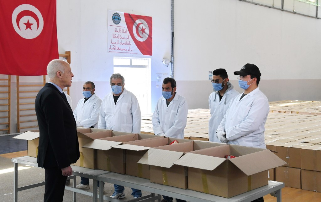 Tunisian President Kais Saied takes part in the distribution of aid packages in Gammarth on 5 April (Tunisian Presidency/AFP)