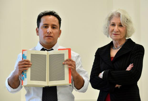 Yahdih Ould Salahi poses with a redacted copy of Mohamedou Salahi's, his older brother, memoirs (AFP)