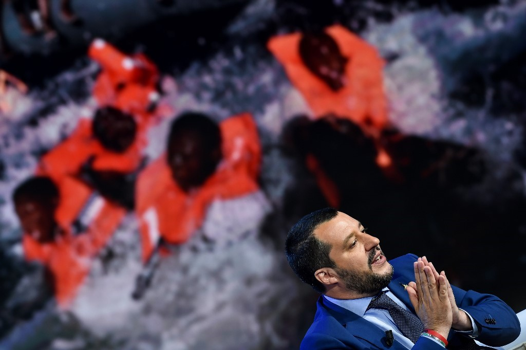 "Italy's Interior Minister and Deputy Prime Minister Matteo Salvini speaks during the Italian talk show ""Porta a Porta"", broadcast on Italian channel Rai 1, in Rome, on June 20, 2018, as picture of migrants is seen in the background."