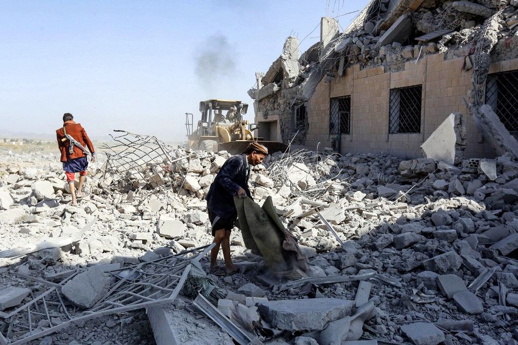 People inspect a destroyed Houthi detention centre south of Sanaa on 1 September (AFP)