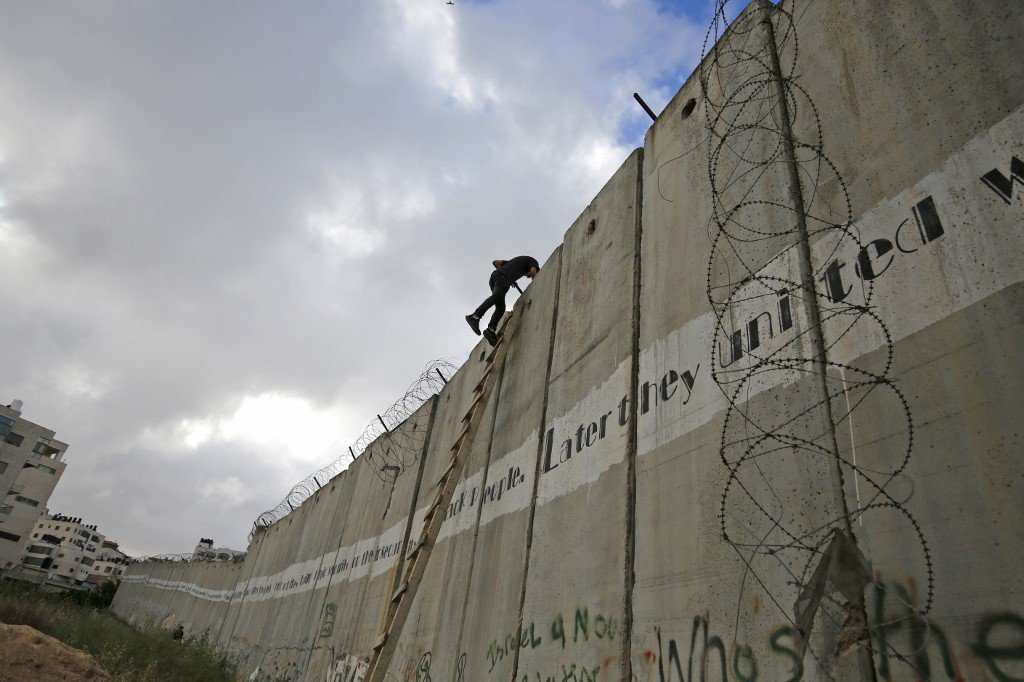 A Palestinian youth climbs a section of Israel's separation wall in Jerusalem on 10 May (AFP)
