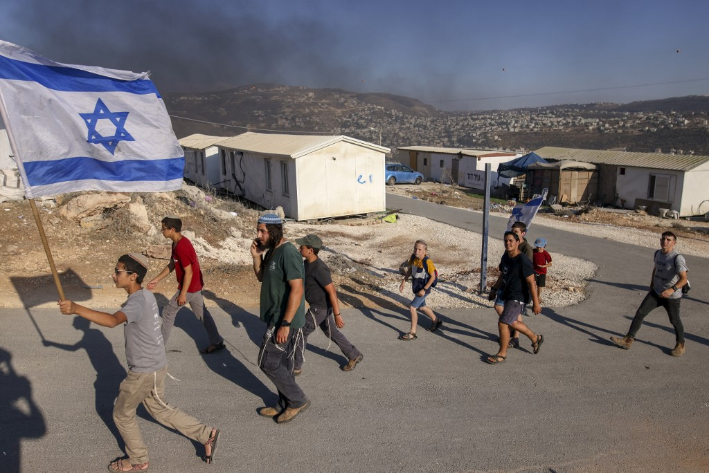 Israeli settlers march in a new outpost in the occupied West Bank on 21 June 2021 (AFP)