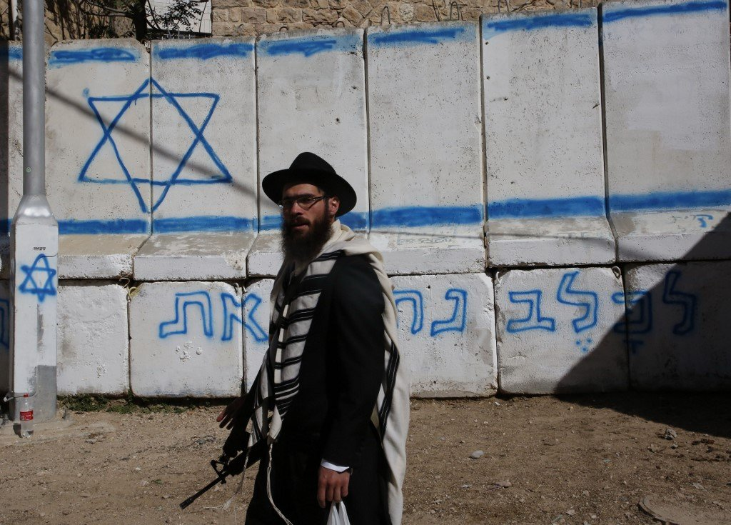 An armed Israeli settler stands near the Ibrahimi Mosque in Hebron in 2018 (AFP)