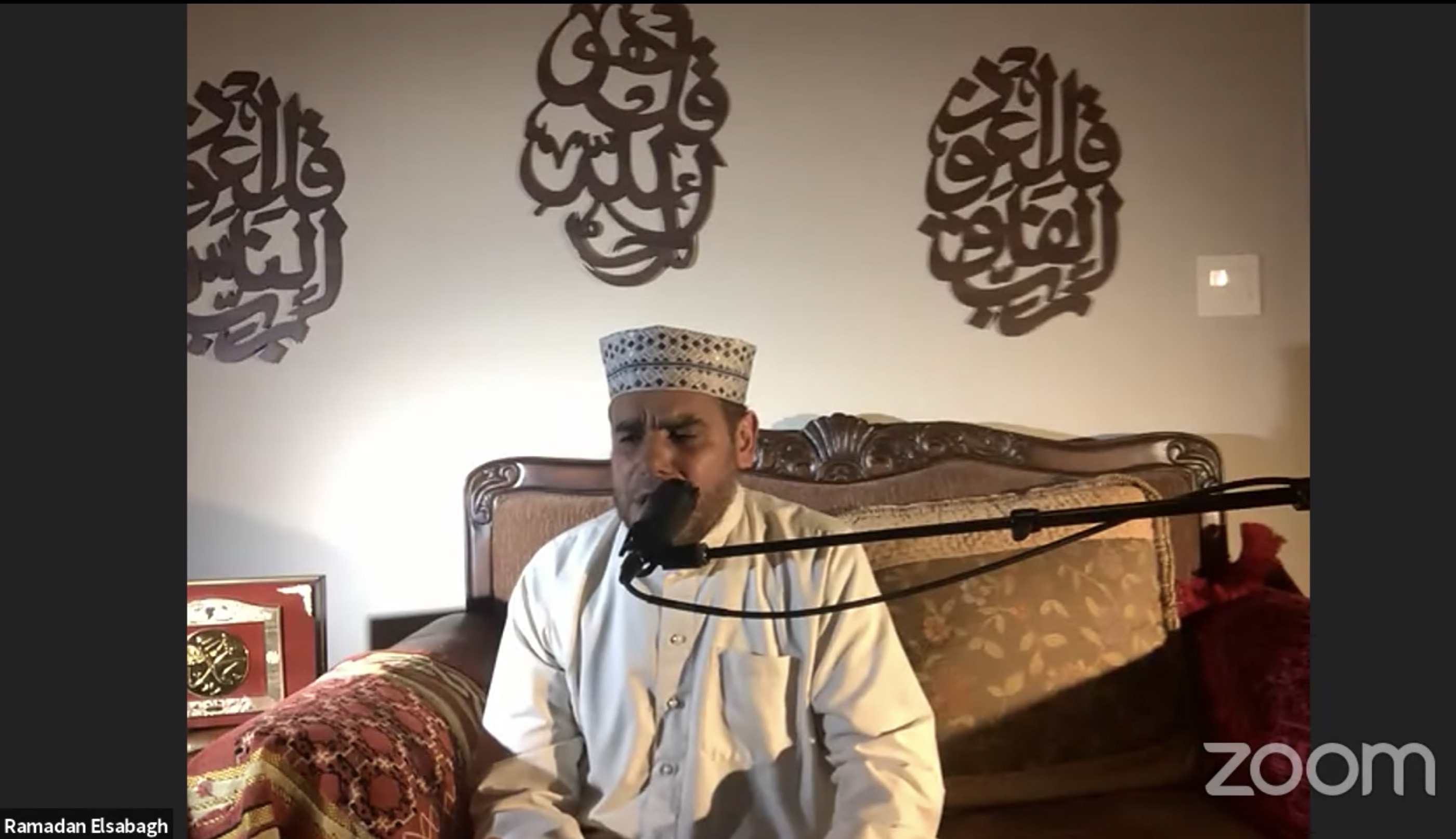 An Imam recites Qur'an while sitting down.