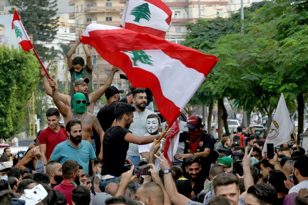 Demonstrators wave Lebanese flags in the southern city of Sidon on 18 October 2019 (AFP)