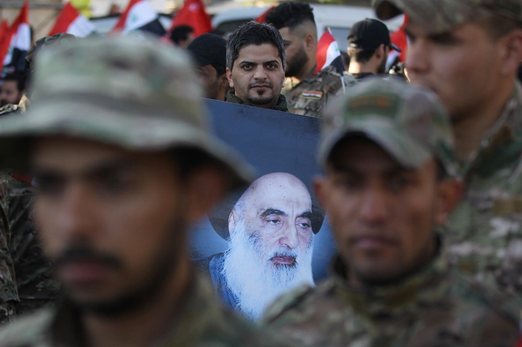 A member of Hashed al-Shaabi holds a picture of Iraq's top Shiite cleric Grand Ayatollah Ali Sistani during the funeral procession of fellow comrades in Baghdad on December 31, 2019,