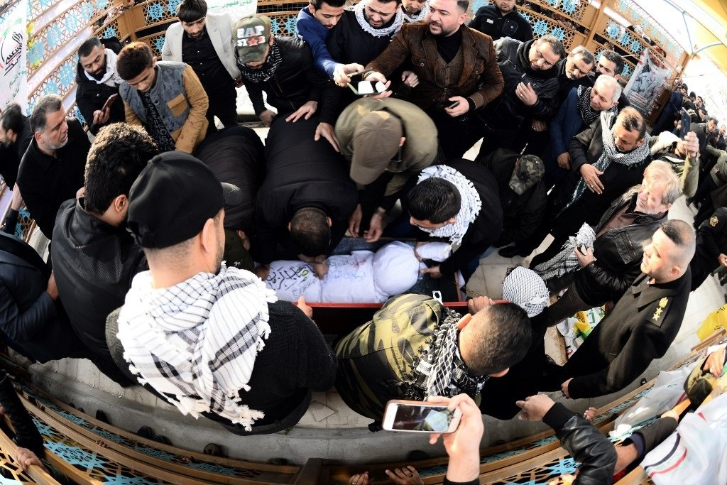 Iraqi mourners, including members of Hashed al-Shaabi, gather around the coffin of Muhandis in Najaf on Wednesday (AFP)