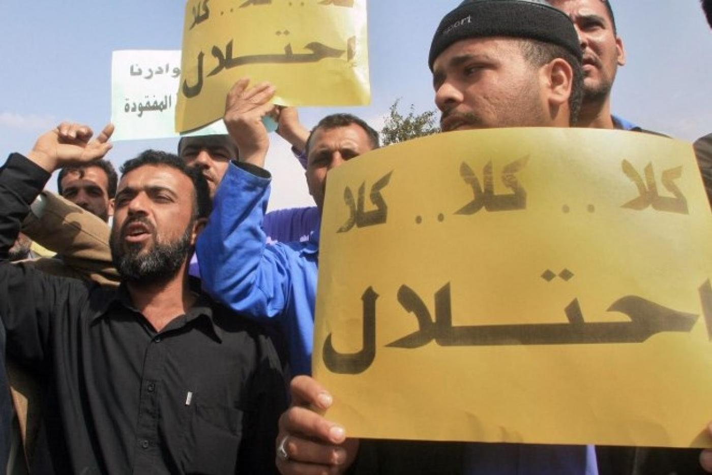 "Employees of the southern Basra province energy company carry placards that read ""no for occupation"" and shout slogans during a demonstration in front of the British consulate in Basra, 2007 (AFP)"
