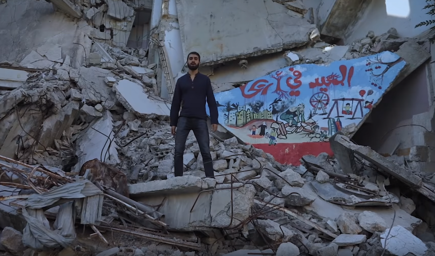 Amir in music video near rubble