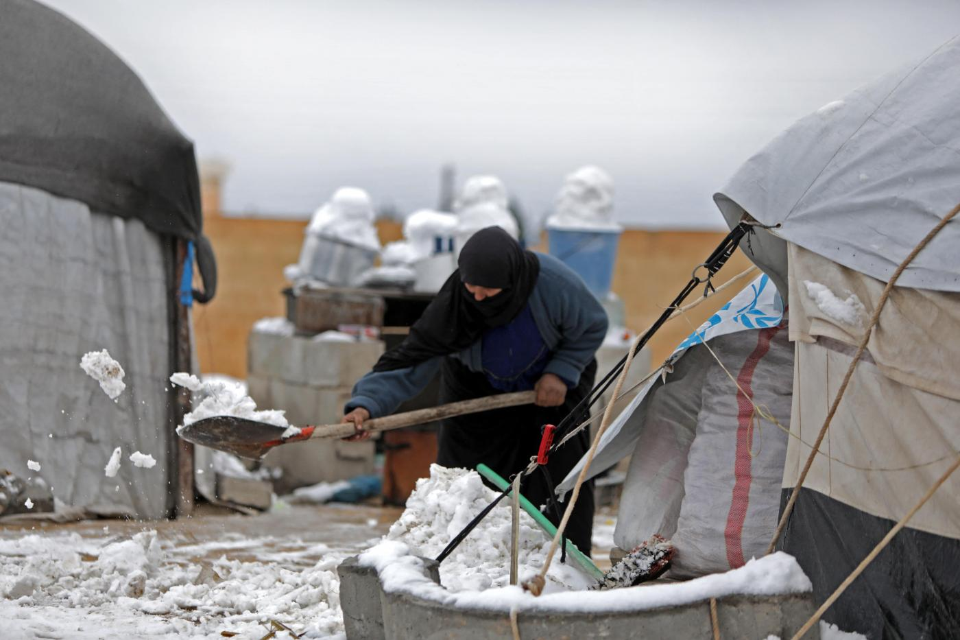 A woman who fled pro-regime forces attacks in northeastern Syria, clears the snow in front of a tent at camp for displaced people in the northern Syrian town of Tal Abyad by the border with Turkey, on February 13, 2020. (Bakr ALKASEM/AFP)