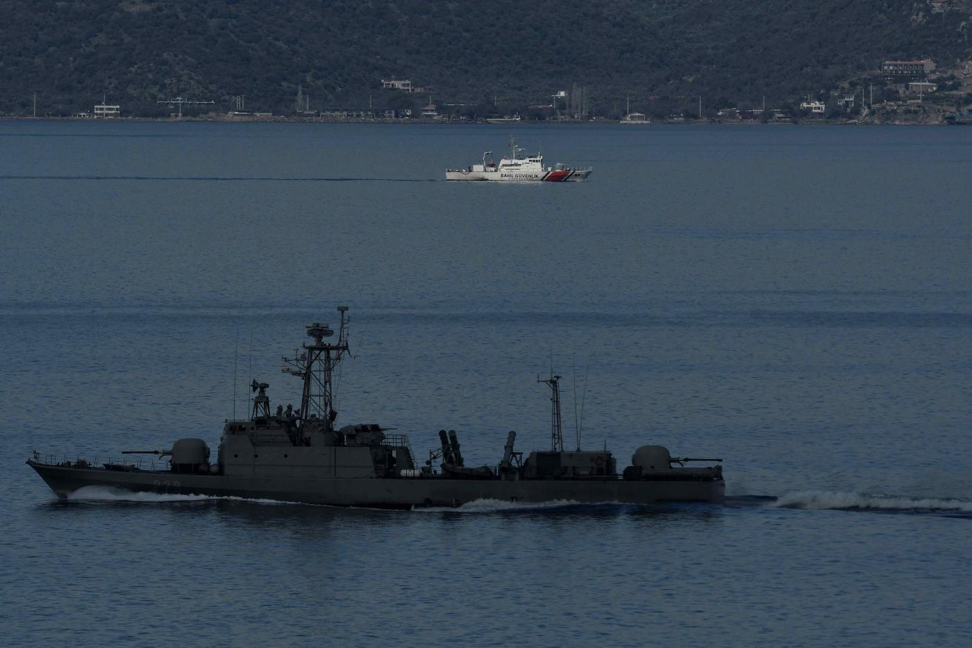 A Turkish military ship passes a coastgard patrol boat near the island of Lesbos (AFP)