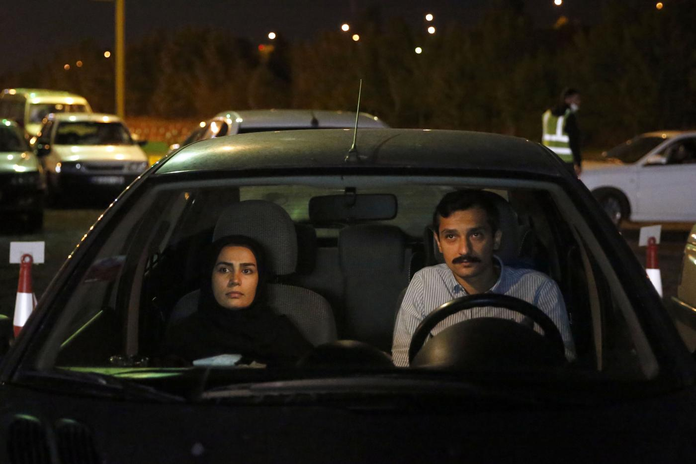 Iranians sitting in their vehicles attend a drive-in religious ceremony