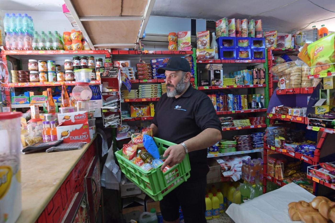 Un employé tunisien d'une épicerie prépare des rations d'aide alimentaire pour les plus démunis, à Tunis le 8 mai 2020 (AFP)