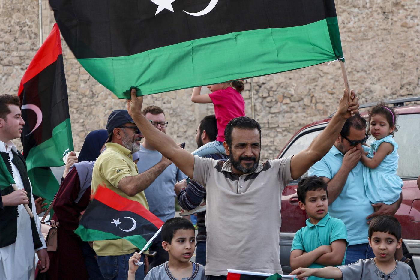 Un homme brandit un drapeau national libyen au cours de célébrations dans la capitale Tripoli, après que le Gouvernement d'union nationale (GNA) reconnu par l'ONU a déclaré avoir repris le contrôle total de la capitale le 4juin (AFP)