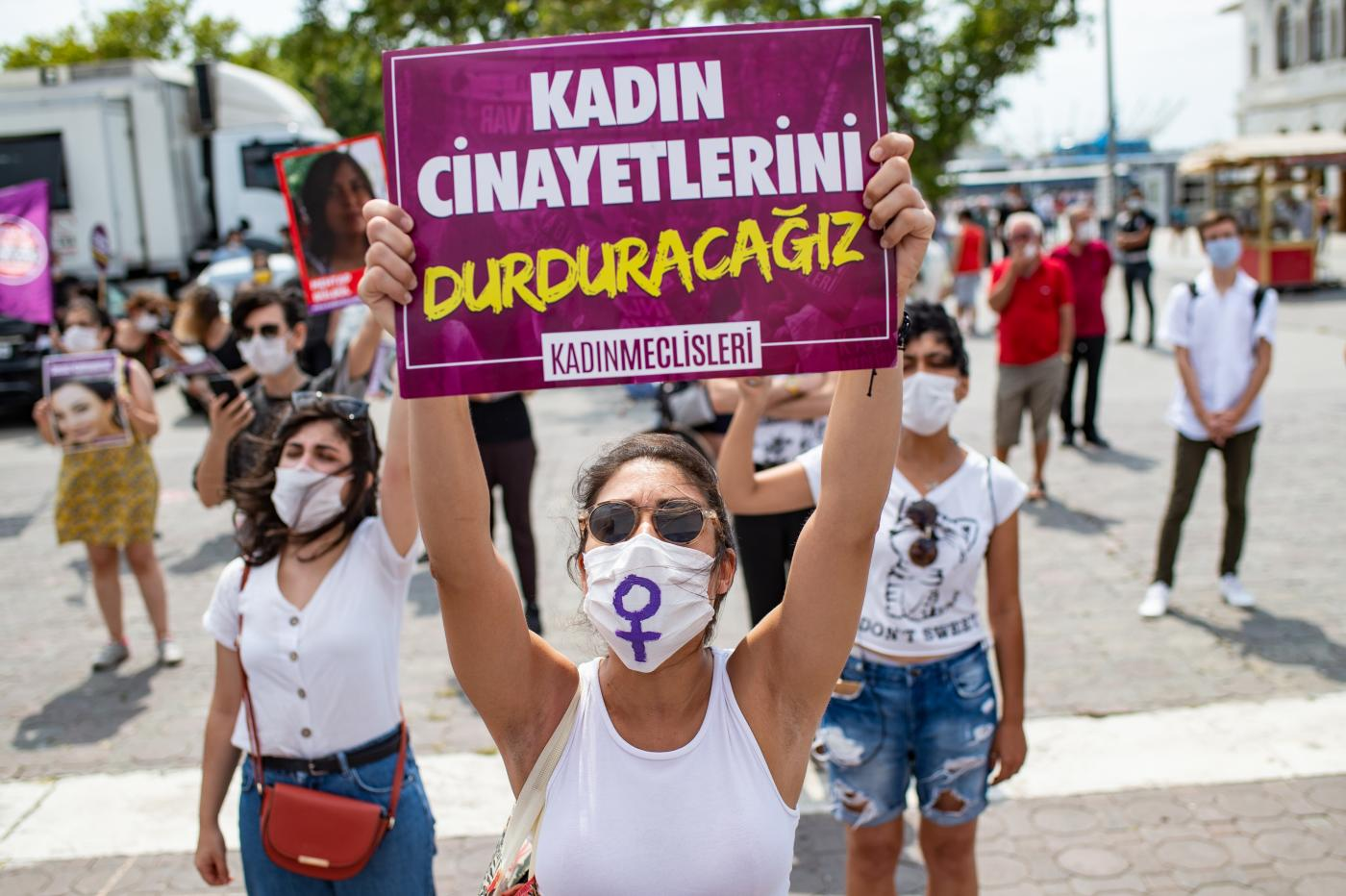 A demonstrator wearing a protective face mask, holds a placard reading 'stop femicides' during a protest called by KCDP (We Will Stop Femicides Platform - Kadin Cinayetlerini Durduracagiz Platformu) and Women's Assemblies, for a better implementation of the Istanbul Convention and the Turkish Law 6284 for protection of the family and prevention of violence against women, in Istanbul, Turkey (AFP)